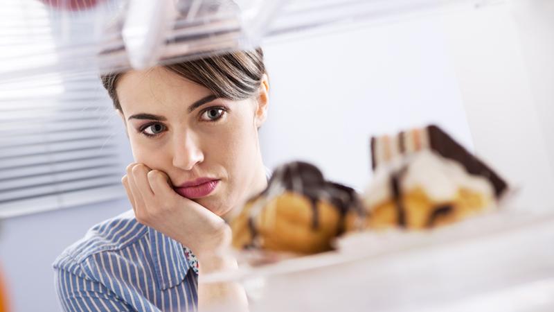 wanita sedang melihat kue-kue di dalam kulkas